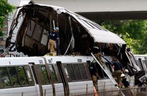 After the collision of two trains on the red line of the Washington DC Metro system, the top part of one train car rests atop the lead cars of the train that crashed into it from behind.  Workers from the Loudon County Fire Department are climbing ladders and walking on top of the train.